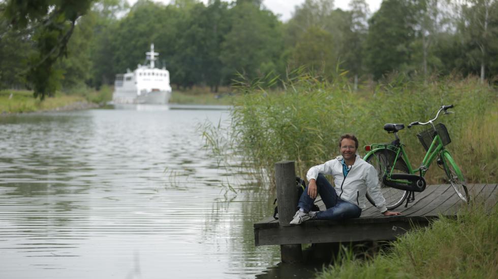Martin Örnroth sitter på brygga vid Göta Kanal med godis från Cloetta